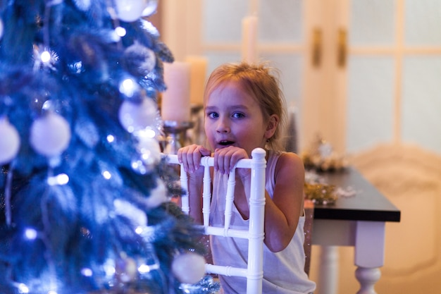 Beautiful little girl in christmas decorations and waiting for santa