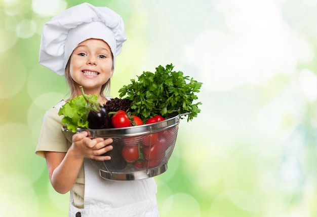 Beautiful little girl  in   cook hat holding bowl with vegetables