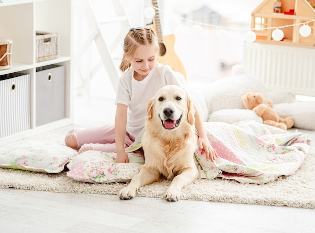 プレイルームの床に毛布でかわいい犬を覆う美しい少女
