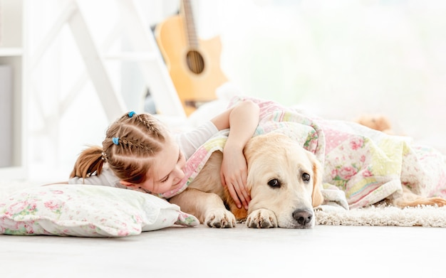 Beautiful little girl covering cute dog
