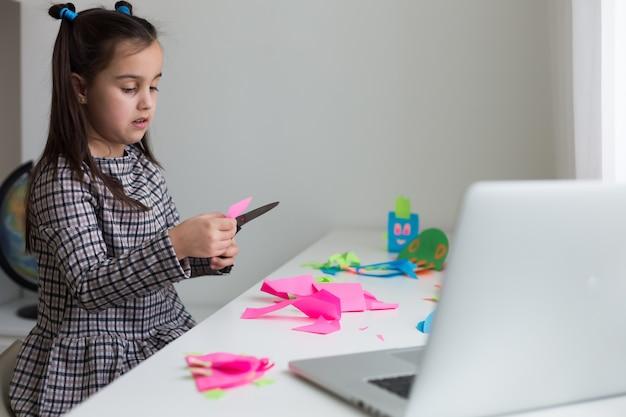 アートレッスンクラスでハサミで紙を切って美しい少女。子供の教育のコンセプトです。キッズクラフト。スクーに戻る