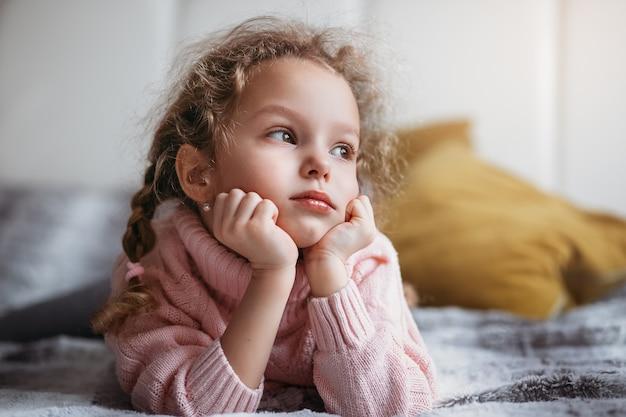 Красивая маленькая девочка мечтает и смотрит в окно, лежа на диване