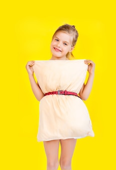 Beautiful little girl in a dress made of pillows on a yellow background quarantine