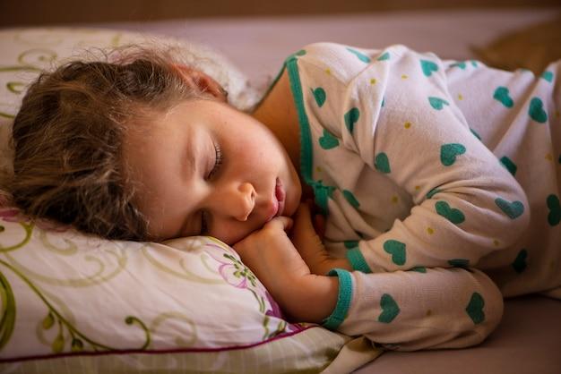 Красивая маленькая девочка, одетая в пижаму и спящая