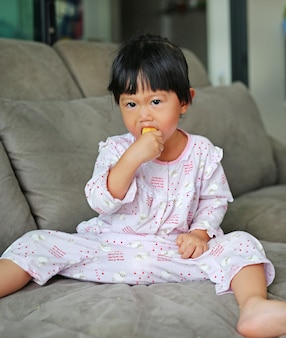 Beautiful little girl eating banana in pajamas on sofa bed