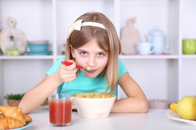 自宅のキッチンで朝食を食べる美しい少女