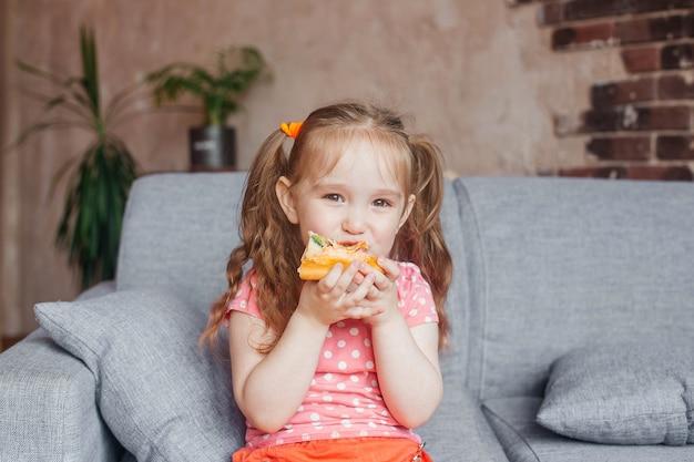 家でピザを食べて美しい少女