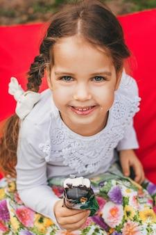Красивая маленькая девочка ест мороженое летом
