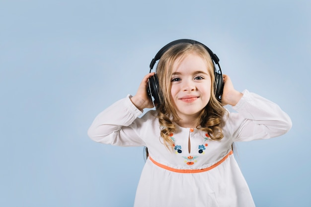 Beautiful little girl enjoying the music on headphone against blue backdrop