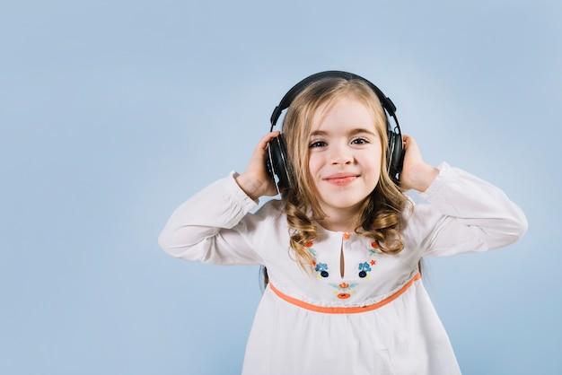 파란색 배경으로 헤드폰에서 음악을 즐기는 아름다운 소녀