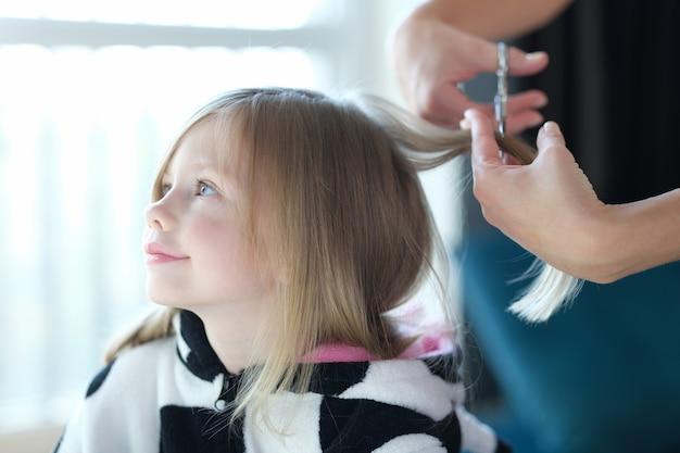 Красивый парикмахер маленькой девочки отрезает волосы. стрижка для детей в домашних условиях