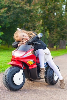 Beautiful little girl having fun on her toy motorcycle