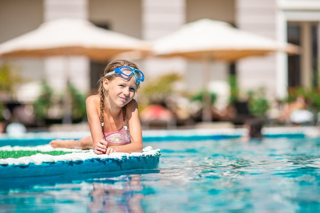 Beautiful little girl having fun near an outdoor pool
