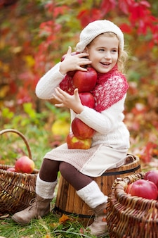 Beautiful little girl holding apples in the autumn garden. little girl playing in apple tree orchard. toddler eating fruits at fall harvest. outdoor fun for children. healthy nutrition