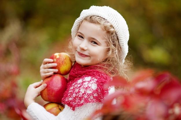 가을 정원에서 사과를 들고 있는 아름다운 소녀. . 사과 나무 과수원에서 노는 어린 소녀. 가을 수확기에 과일을 먹는 유아. 아이들을 위한 야외 활동. 건강한 영양