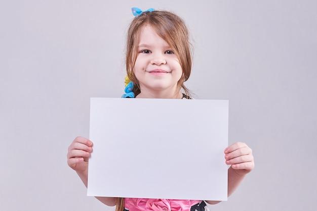 Красивая маленькая девочка держит в руках белый лист бумаги