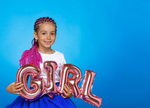 아름 다운 작은 소녀 복사 공간 파란색 벽에 비문 소녀와 풍선을 손에 들고. 가로보기.
