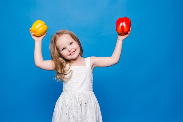 Beautiful little girl holds in bell pepper isolated on blue wall