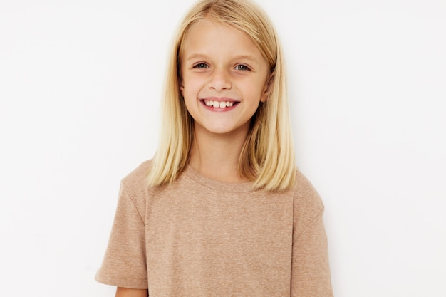 Красивая маленькая девочка в бежевой футболке изолированный фон