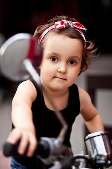 Красивая маленькая девочка в байкерском стиле на мотоцикле.