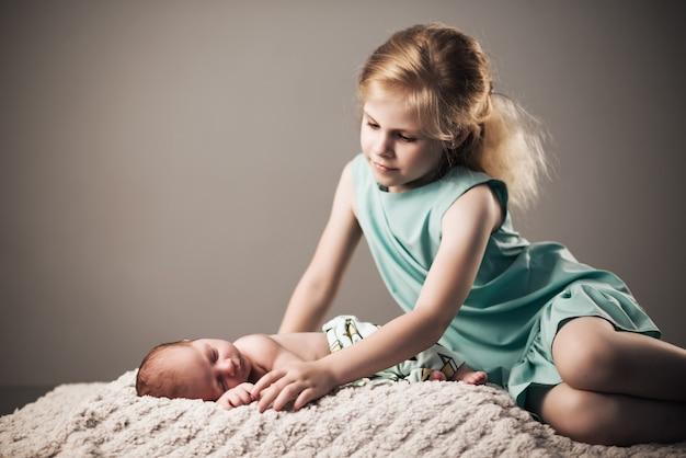 青いドレスを着た美しい少女は、灰色の壁に格子縞の上に横たわっている彼女の小さな魅力的な眠っている新生児の弟を見ています