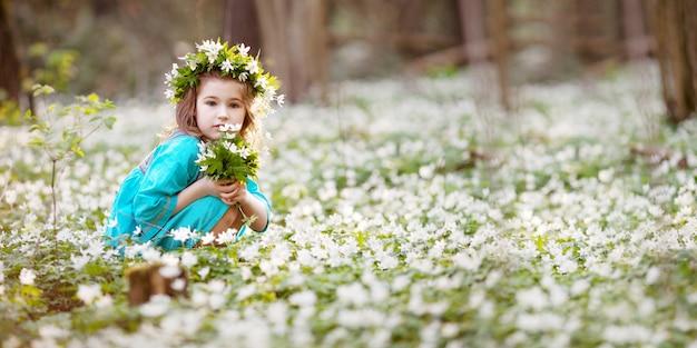 봄 나무에 걸어 파란 드레스에 아름 다운 작은 소녀. 머리에 꽃에서 화 환으로 예쁜 여자의 초상화. 부활절 시간. 눈을 심는 귀여운 정원사. 공간을 복사하십시오. 배너