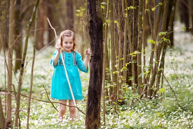 春の森を歩く青いドレスを着た美しい少女。頭の上の花からの花輪を持つかわいい女の子の肖像画。イースターの時間。雪を植えるかわいい庭師が値下がりしました。