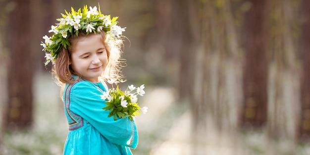 봄 나무에 걸어 파란 드레스에 아름 다운 작은 소녀. 머리에 꽃에서 화 환으로 예쁜 여자의 초상화. 부활절 시간. 눈을 심는 귀여운 정원사.