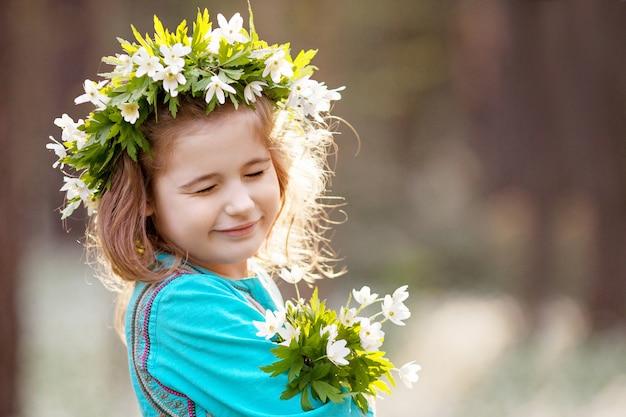 春の森を歩く青いドレスを着た美しい少女。頭の上の花からの花輪を持つかわいい女の子の肖像画。夏に野外で遊ぶ子供。イースターの時間。コピースペース