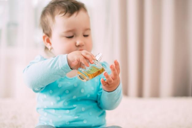 그녀의 손에 향수와 블루 재킷에 아름 다운 작은 소녀