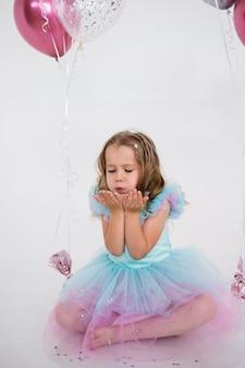 축제 드레스를 입은 아름다운 소녀가 앉아서 흰색 배경에 색종이 조각을 불고 있습니다. 축제 배경