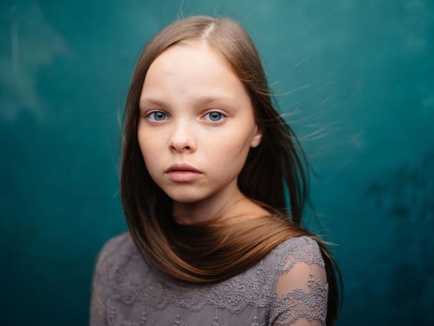 Красивая маленькая девочка в сером платье крупным планом обрезанный вид светлых волос бирюзового цвета.