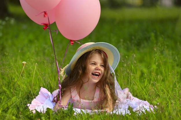 帽子と風船で笑っている美しい少女。高品質の写真