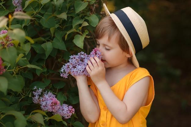 ライラックの花の近くの帽子の美しい少女