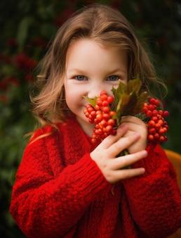 Красивая маленькая девочка в красной вязаной куртке с рябиной осенний парк