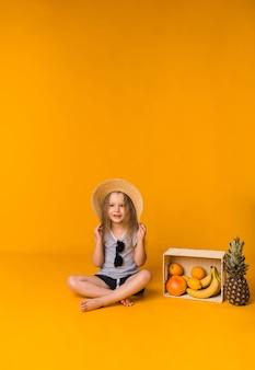 밀짚 모자와 선글라스에 아름다운 소녀는 노란색 표면에 과일 바구니와 함께 앉아 카메라를 찾습니다
