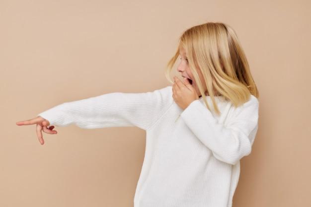 Красивая маленькая девочка в свитере гримасничает на бежевом фоне