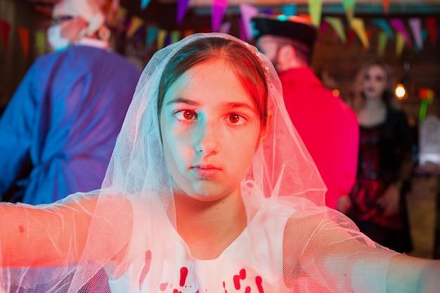 Красивая маленькая девочка в платье для прополки на карнавале хэллоуина. жуткое выражение. празднование хэллоуина.