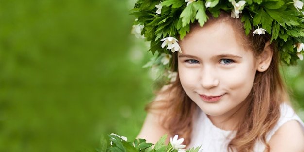 春の木の白いドレスを着た美しい少女。頭の上の春の花からの花輪を持つかわいい女の子。イースターの時間。バナー。コピースペース