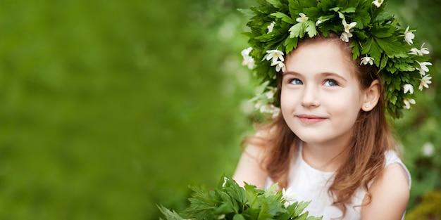 春の木の白いドレスを着た美しい少女。頭の上の春の花からの花輪を持つかわいい女の子