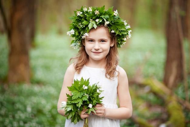 봄 나무에 하얀 드레스를 입고 아름 다운 작은 소녀. 머리에 봄 꽃에서 화 환을 가진 예쁜 소녀의 초상화.