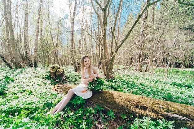 倒れた木の上に座って白いドレスを着た美しい少女。彼女の頭とスノードロップに帽子をかぶったかわいい女の子の肖像画。