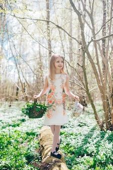 倒れた木の上を歩く白いドレスを着た美しい少女。彼女の頭に帽子とスノードロップのバスケットを持つかわいい女の子の肖像画。
