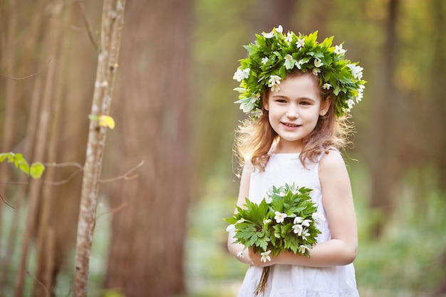 하얀 드레스를 입고 아름 다운 소녀는 봄 나무에서 산책. 머리에 봄 꽃에서 화 환을 가진 예쁜 소녀의 초상화.