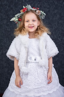 크리스마스 화환이 있는 흰색 모피 코트를 입은 아름다운 소녀