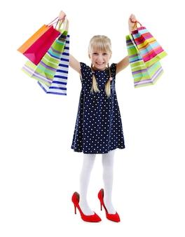 흰색에 고립 된 쇼핑 가방과 함께 엄마의 신발에 아름 다운 작은 소녀