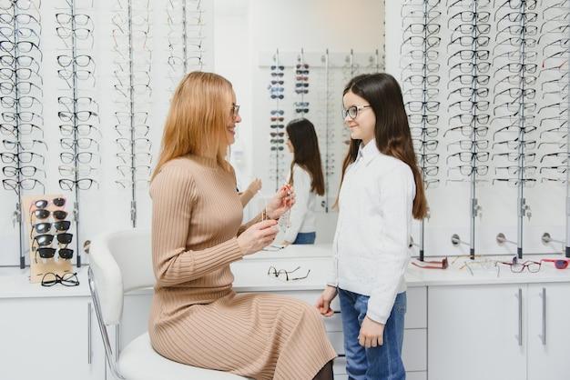 Красивая маленькая девочка в магазине оптики вместе с мамой выбирают новые очки
