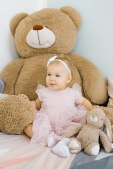 분홍색 옷을 입은 아름다운 소녀가 침대에 거대한 테디베어와 토끼 장난감을 가지고 앉아 있습니다.