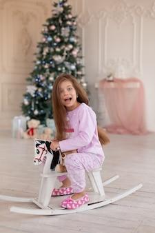 Красивая маленькая девочка в розовой пижаме радуется деревянному подарку от санта-клауса на рождество