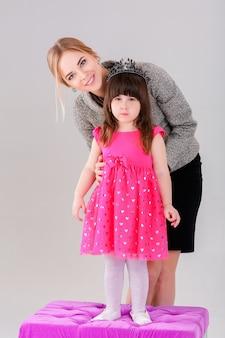 Красивая маленькая девочка в розовом платье принцессы с короной и красивой мамой, обнимающейся на сером фоне.